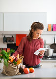 Woman in kitchen comparing shopping list to items in bag