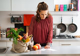 Woman in kitchen reading shopping list on counter with shopping