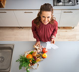From above, woman smiling in kitchen with fall fruit and veg