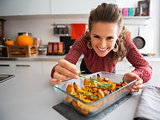 Smiling elegant woman preparing roasted pumpkin dish