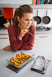 Pensive woman at kitchen counter with closeup of pumpkin