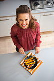 Smiling woman looking up in kitchen cutting roasted vegetables