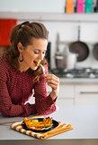 Elegant woman taking a bite of roasted pumpkin