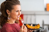 Profile of woman holding bite of roasted pumpkin on a fork
