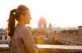 Elegant woman looking out at sunset over the city of Rome