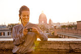 Smiling elegant woman checking photos on camera in Rome