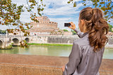 Woman from behind taking photo of Castel St'Angelo in Rome