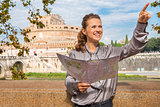Smiling woman holding map and pointing near Castel St'Angelo