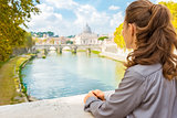 Elegant woman looking out onto Tiber River in Rome