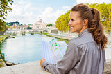 Profile of smiling woman holding map in Rome on Tiber River