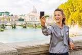 Smiling woman taking selfie in Rome by Tiber River