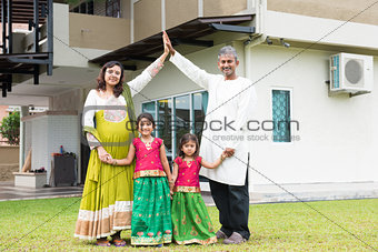 Asian Indian family outside their new home