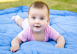 Cute little baby girl is smiling and playing on grass