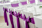 Close-up of white wedding chairs with purple ribbon