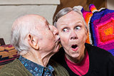 Elderly Gentleman Kissing Elderly Woman on Cheek