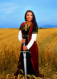 Smiling Young woman with ornamental dress and sword in hand  standing on a wheat field with sunset. Natural background.