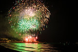 Fireworks display over sea with reflections