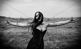 Crying sad goth girl in the autumnal field. Black and white