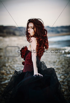 Beautiful sad goth girl standing on sea shore. Rear view