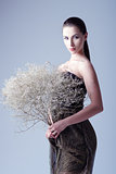 Studio fashion shot: beautiful young woman in dress holding bouquet of withered flowers