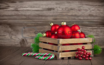 Christmas balls in box with fir on wooden board