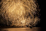 Golden fireworks falling over sea with reflections