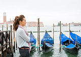 Woman standing in profile in Venice with gondolas in background