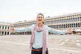 Happy woman tourist rejoicing on St. Mark's Square
