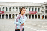 Woman tourist on empty St. Mark's Square looking over shoulder