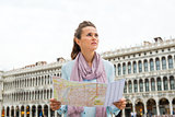 Woman holding map on St. Mark's Square looking into distance