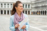 Smiling woman tourist holding map in empty St. Mark's Square
