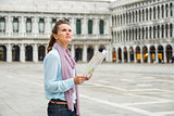 Woman in profile holding map looking up on St. Mark's Square