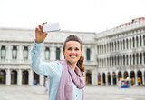 Smiling woman tourist taking a photo on St. Mark's Square