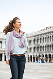 Happy woman tourist walking through St. Mark's Square