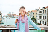 Smiling woman holding scarf standing on Bridge