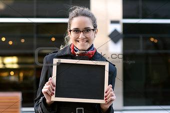 Business woman holding a chalkboard.
