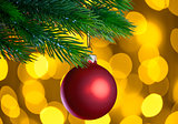 Red Christmas Ball and Green Fir Branch on the Blurred Background with Bright Yellow Holiday Lights