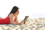 Girl reading an ebook or tablet on the beach