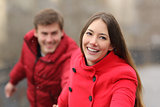 Happy couple running towards camera in winter