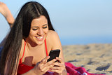 Teen girl texting on the smart phone on the beach