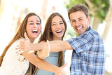 Three happy teenagers laughing with thumbs up
