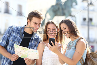 Three tourist friends consulting gps on smart phone