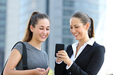 Two businesswomen talking about smart phone