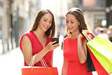 Two fashion shoppers shopping with a smart phone