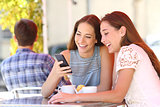 Two friends or family sharing a smart phone in a coffee shop