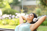 Woman listening to music and relaxing in a park