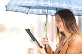 Woman reading ebook or tablet under the rain