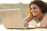 Woman using a laptop in a park at sunset