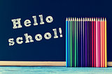 pencil crayons and text hello school written on a chalkboard