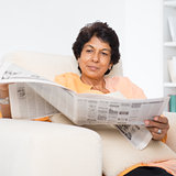 Indian mature woman reading news paper